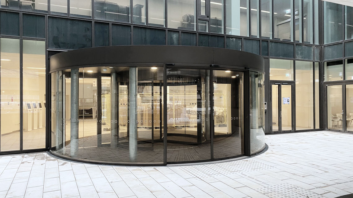 Smart glass façade with revolving door and GEZE Slimdrive SC at the patient entrance.