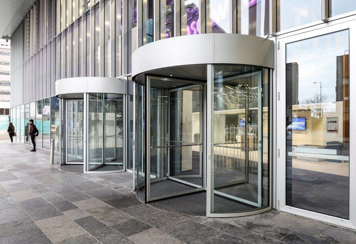Zwei große, manuelle Karusselltüren fügen sich perfekt in die Fassade des City Campus ein.