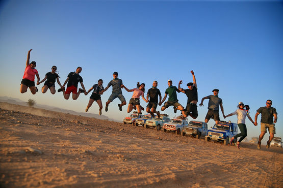 Entrants in the 4L Trophy leap into the air with joy on their arrival in Morocco.
