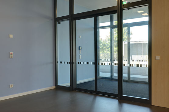 Interior view of entrance to Rheinhausen primary school, fitted with Slimdrive sliding door system for escape and rescue routes plus GEZE INAC access control system.