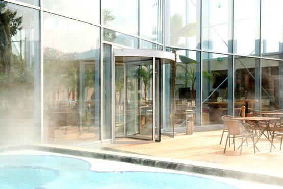 GEZE revolving door in water, entrance to the outdoor pools.