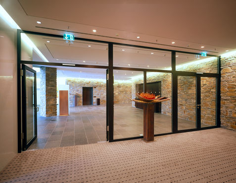 Corridor area with glass partitioning wall and open glass door.