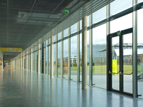 Glass swing door system in the façade of the new trade fair.