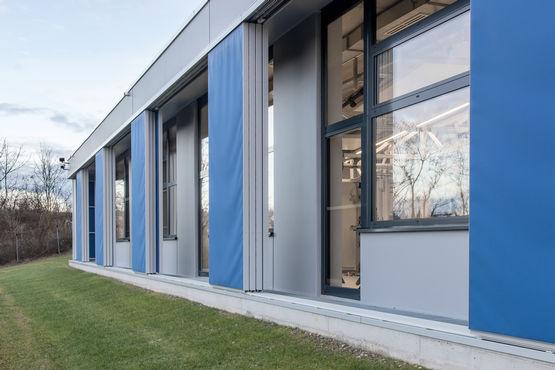 Intelligente Fassadentechnik: Bei Sonne fährt die Verschattung automatisch aus. Fenster öffnen oder schließen je nach Außentemperatur.