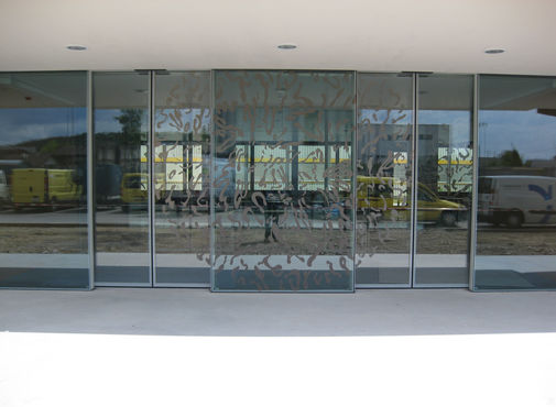 Glass sliding doors with sun designs in the main entrance.