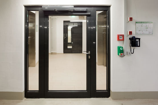 Electrohydraulic swing door drive system for 2-leaf fire and smoke protection doors with integrated closing sequence control in the retirement complex of Augustinum, Stuttgart.