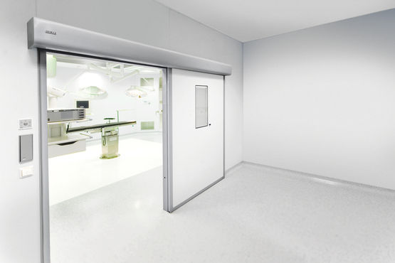 Automatic linear sliding door system for large heavy doors in areas with increased hygiene demands