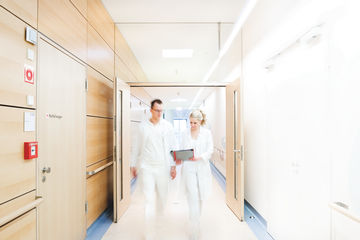 Hospital staff passing through a double-leaf door