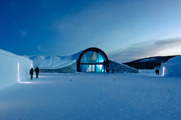 Exterior view of the ICEHOTEL with glass façade and sliding door.