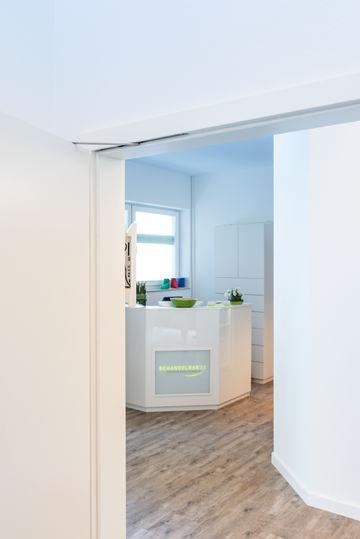 Acesso à sala de tratamento com a porta aberta: Os travões das portas mantêm as portas abertas de forma segura na posição predefinida. Foto: Jürgen Pollak para a GEZE GmbH