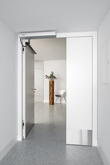 An open single-leaf fire protection door at the Fux Campagna residential home, equipped with a GEZE Powerturn F.