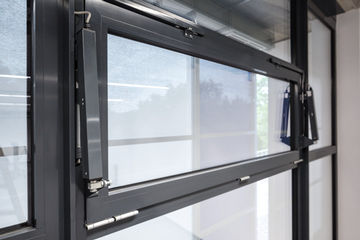 Opening and locking system OL 350 EN, installed in an office building. System solution with horizontal profiling spindle drive E 350 N and a bracket set with locking mechanism Mechanical locking mechanism at the main closing edge by the spindle drive Large opening widths with small spindle stroke. Only Solo operation possible. Opening and locking of inward opening windows with bottom-hung, top-hung and side-hung leaves Installation on wooden, plastic or metal windows. Frame installation.